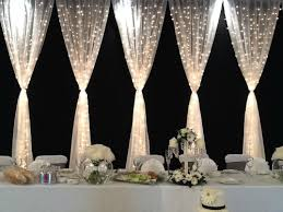 wedding venue backdrop incorporating christmas lights into your wedding decor