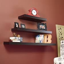 three layer dark brown wooden wall shelf on red brick painted wall