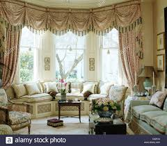 swagged tailed silk curtains on bay window above window seat with