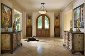 interior high ceiling foyer lighting with statues on two carved