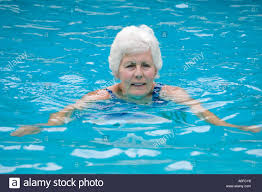 elderly woman enjoying a swim in outside pool mombasa kenya stock