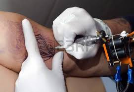 tattoo artist makes the tattoo on arm stock photo picture and