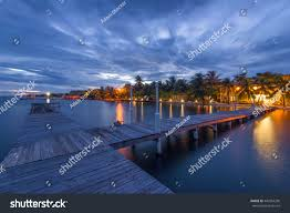 boardwalk sunset placencia belize trees lights stock photo