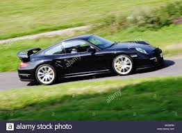 porsche side view profile side view of a black porsche 911 997 turbo driving fast on