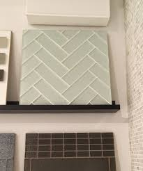 black vertical subway tile corner shower design with clear glass