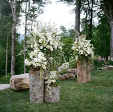 backyard wedding altar pretty floral arrangements on cut logs