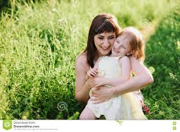 happy beatiful mom kisses and hugs daughter on nature in sunset
