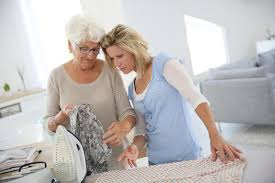 elderly woman clothes senior woman with housekeeper ironing clothes stock photo image