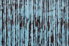 corrugated steel fence panel with flaking and peeling paint in