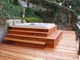 above wooden deck tub with stairs surrounded by lush climbing