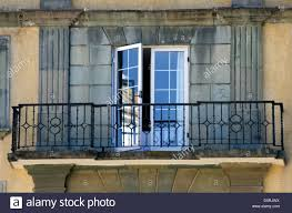 french doors open onto a wrought iron balcony overlooking the