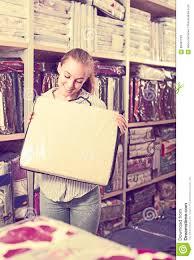 young woman customer choosing for beautiful bed linen stock photo