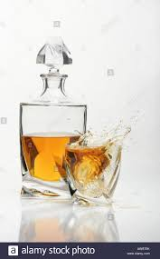 drink splash crystal glass of whisky and carafe pour whiskey with cubes ice