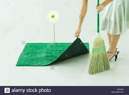 Outdoor Turf Rug by Woman Sweeping Under Artificial Turf Rug Waist Down Stock Photo