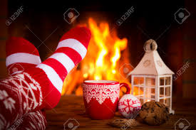 Flame And Comfort Woman At Home Feet In Christmas Socks Near Fireplace Relaxing