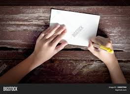 pen writing on paper view of kid hand with yellow pen writing on paper note or postcard top view of kid hand with yellow pen writing on paper note or postcard on old wooden