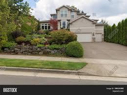 How Big Is A Three Car Garage by Traditional House With Three Car Garage Frontyard Garden Lush
