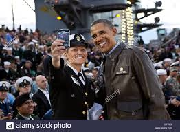 president barack obama has his picture taken with a female sailor