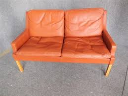 two seat burnt orange leather sofa by rud thygesen and johnny