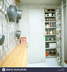 open door to larder cupboard with shelves in galley kitchen with
