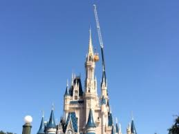 christmas lights being hung on cinderella castle the main street