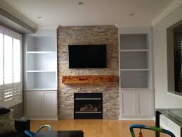 white marble fireplace with unstained wooden mantel shelving also