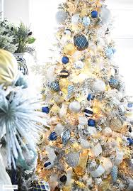 gold christmas tree flocked christmas tree with navy light blue silver and gold ornaments