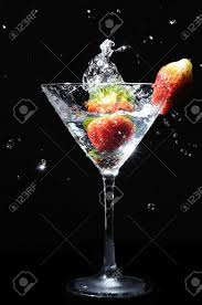 martini strawberry strawberry splashing into martini cocktail drink stock photo
