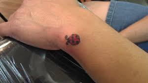 little lady bug tattoo on wrist real photo pictures images and