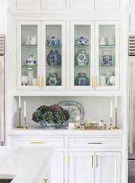 glass cabinets in white kitchen inside a home that expertly mixes tradition and on