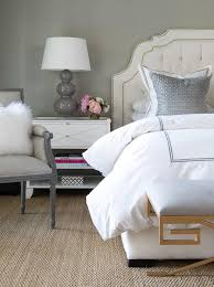 tufted linen headboard with brass nailheads gray lamp on a white