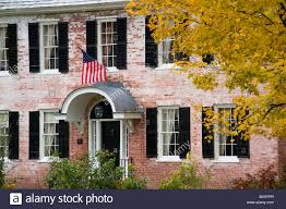 American Flag House An Old Brick House Displaying An American Flag And Surrounded By