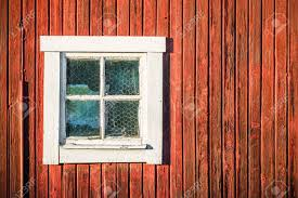 up of square white window in wooden barn wall