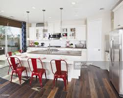 Bar Stools For Kitchen Island by Kitchen Island With Red Bar Stools In House Stock Photo Getty Images