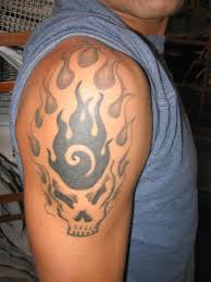 black and grey skull in fire and flame tattoo on man right shoulder