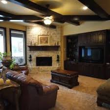 black built ins tv blends in with black shelving units corner fireplace with built