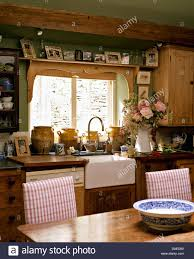 Cottage Kitchen Furniture Photographs On Shelf Above Window And Belfast Sink In Cottage