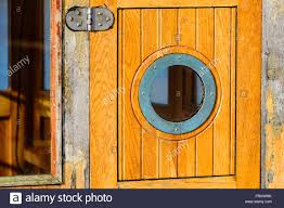detail of a small circular window on a wooden boat cabin door a