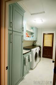 laundry room renovation with turquoise cabinets and marble