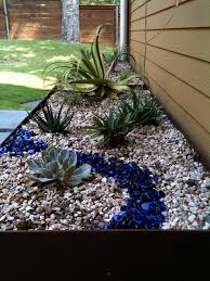 steel planter with succulents river rock and blue glass j