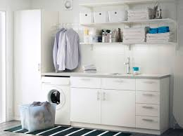 a laundry room with white wall shelves base cabinets with doors