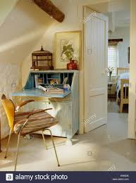 A Study With Walls In by Fifties Chair Beside Pale Blue Painted Desk In Small Attic Study