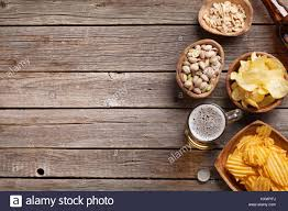 table snack cuisine lager mug and snacks on wooden table nuts chips top view
