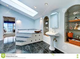 master bathroom with blue marble tile floor and corner bath tub
