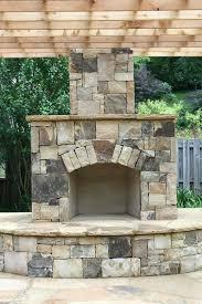 backyard stone corner fireplace outdoor kitchen dinning area patio