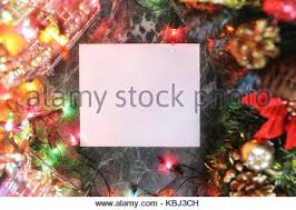 christmas tree branches with blank paper card and golden ribbon on