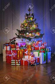 heap of gift boxes under decorated christmas tree in dark stock