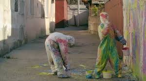 two artists in paint splatter protective coveralls splashing