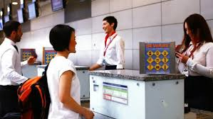 female airport staff checking passport of man at airport check in