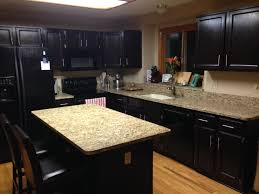 staining oak kitchen cabinets with black color and quartz countertops hardwood floor tiles and island in the middle plus wooden chairs with leather seat and